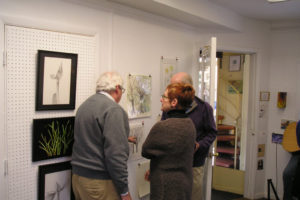 Michael telling fellow Studio 155 artist Vicki Malone about his drawings of the elm trees.
